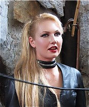 Blond Mistress in black leather whips her slave.