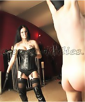 A slave is being whipped by a black haired bombshell